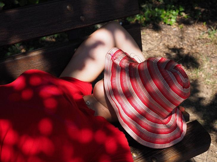 סימנים לכך שאתם סובלים מרגשי נחיתות: אישה שוכבת על ספסל שכובע רחב שוליים על ראשה