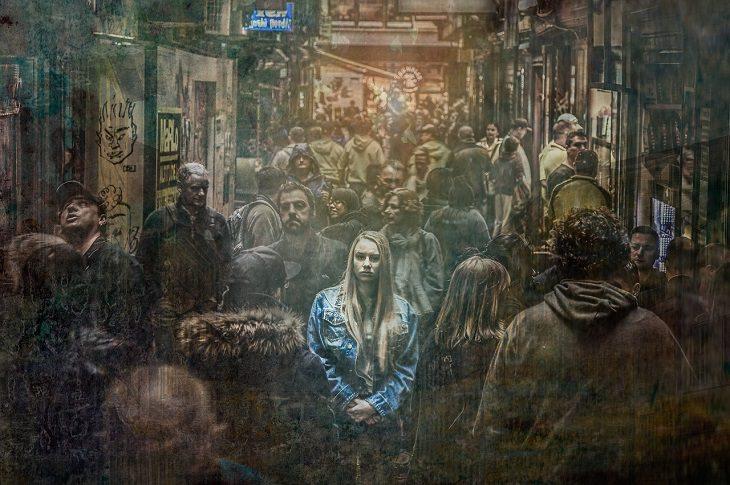סימנים לכך שאתם סובלים מרגשי נחיתות: אישה עומדת בין זרם של אנשים בשוק