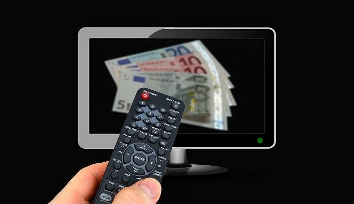 מדריך להוזלת עלויות הטלוויזיה: יד מחזיקה שלט מול טלוויזיה מול מסך עליו מוצגים שטרות כסף