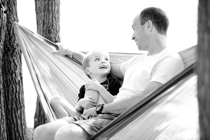 שאלות בנוגע לתיקון בעיות משמעת אצל ילדים: אב ובן יושבים אחד לצד השני על ערסל