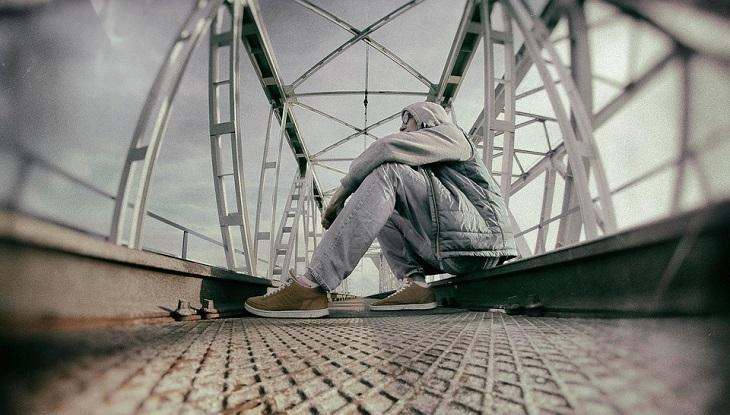 כלים ליישום חשיבה חיובית: אדם מהורהר יושב על גשר