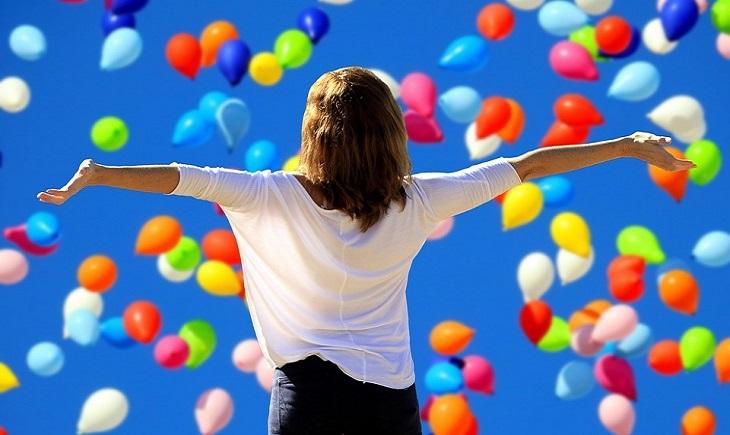 כלים ליישום חשיבה חיובית: אישה מאושרת על רקע בלונים