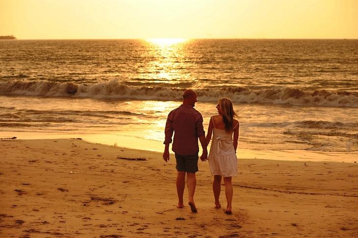 עצות לתחזוק הזוגיות: זוג הולך על חוף הים אל מול השקיעה