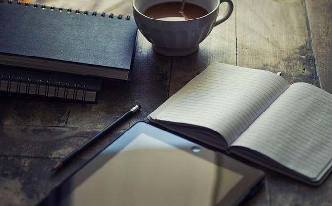 חידון מילים לועזיות בעברית: שולחן עם טאבלט, יומן וכוס קפה