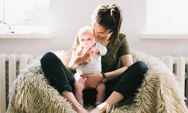 מהי תסמונת הראש השטוח אצל תינוקות: אם יושבת ומרימה את תינוקה בידיה