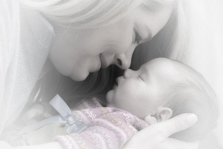 מהי תסמונת הראש השטוח אצל תינוקות: אם אוחזת את התינוקת שלה ומצמידה אף אל אף