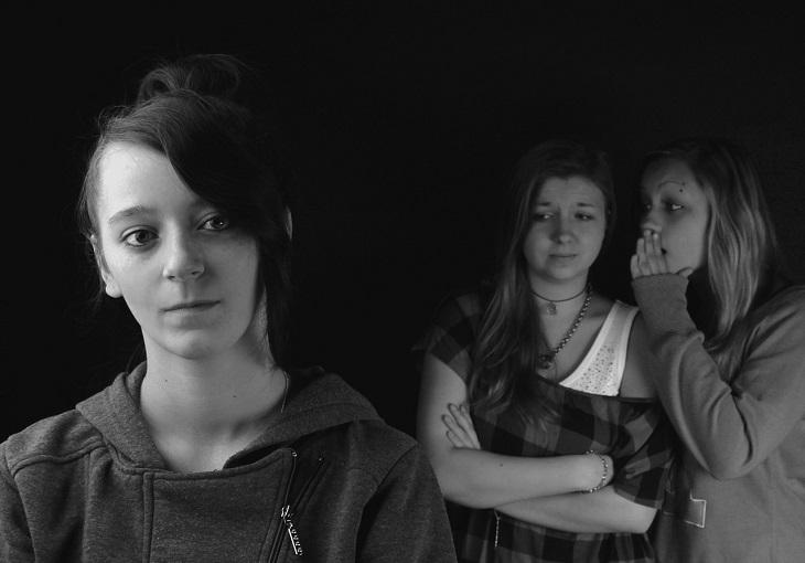 התנהגויות אנוכיות חיוביות: שתי בנות מרכלות מאחורי גבה של מישהי שלישית
