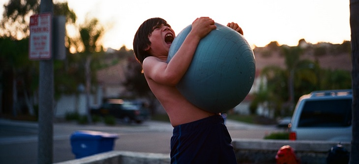 8 סוגי הפרעות נפש: ילד עצבני וצועק, אוחז כדור פיזיותרפיה בידיים ומנסה לפוצץ אותו