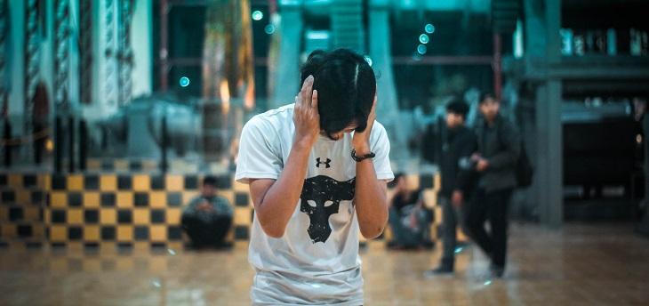 8 סוגי הפרעות נפש: בחור אוחז את שתי אוזניו ומנסה להתרכז