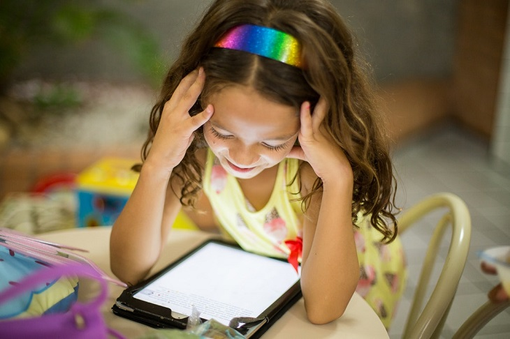 האם סמארטפונים וטאבלטים טובים או מזיקים לילדיכם: ילדה בוהה במסך של טאבלט