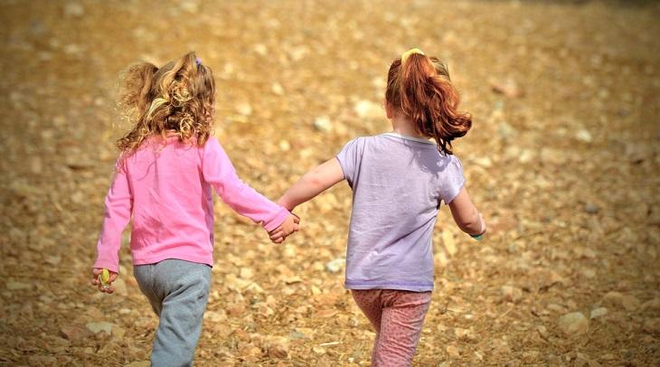 האם סמארטפונים וטאבלטים טובים או מזיקים לילדיכם: שתי ילדות אוחזות יד ביד ורצות