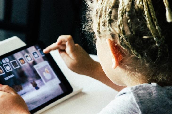 האם סמארטפונים וטאבלטים טובים או מזיקים לילדיכם: ילד לוחץ על מסך של טאבלט