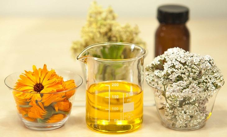 10 סיבות לשימוש בשמן חוחובה: כוסית מעבדה עם שמן ופרחים