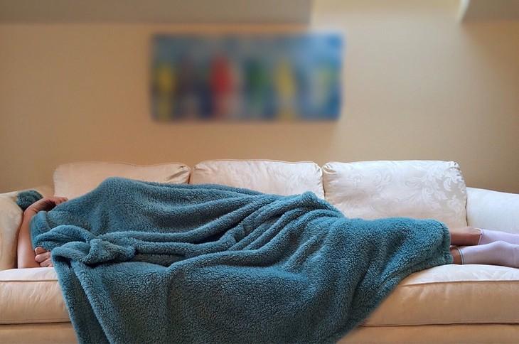 שיטה צבאית להירדמות מהירה: אישה שוכבת על ספה ושמיכה מכסה את כולה