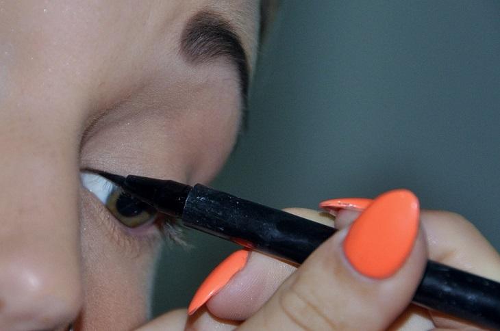 10 סיבות בגללן הראייה שלנו מתדרדרת: אישה מציירת עם עפרון שחור על עפעף העין שלה
