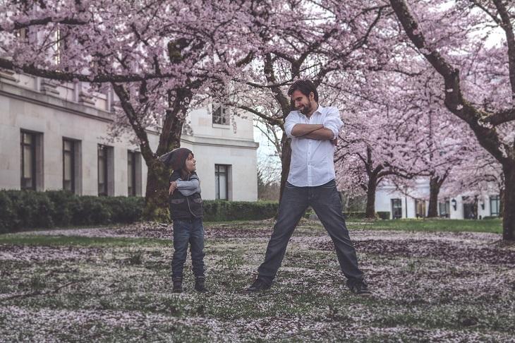 עצות להתמודדות עם ילד עקשן: אב ובנו עומדים זה מול זה בידיים שלובות