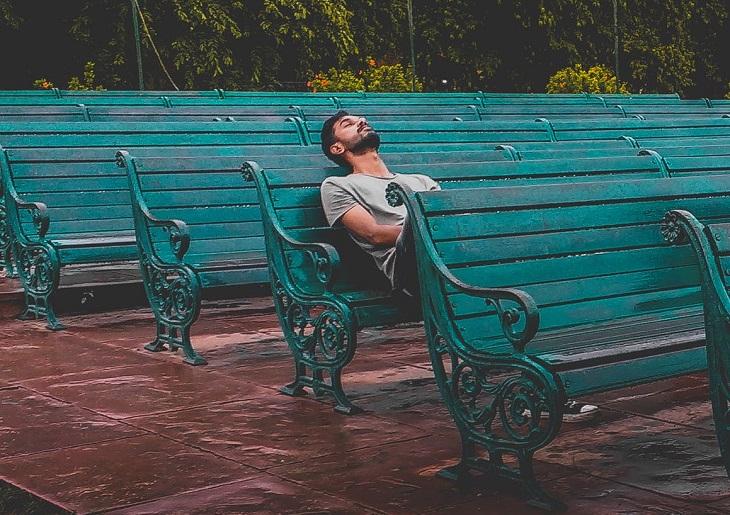 להעביר שעמום בכיף: גבר צעיר נח על ספסל