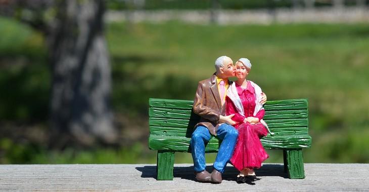 עצות לזוגיות מאושרת: שתי בובות של אנשים מבוגרים יושבות על ספסל והגבר נושק לאשה