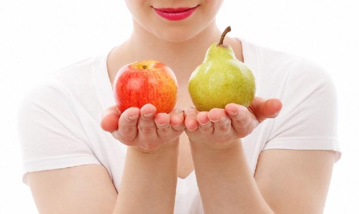 איך מזהים דיכאון בתפקוד גבוה: אישה מחזיקה אגס ותפוח בשתי ידיים