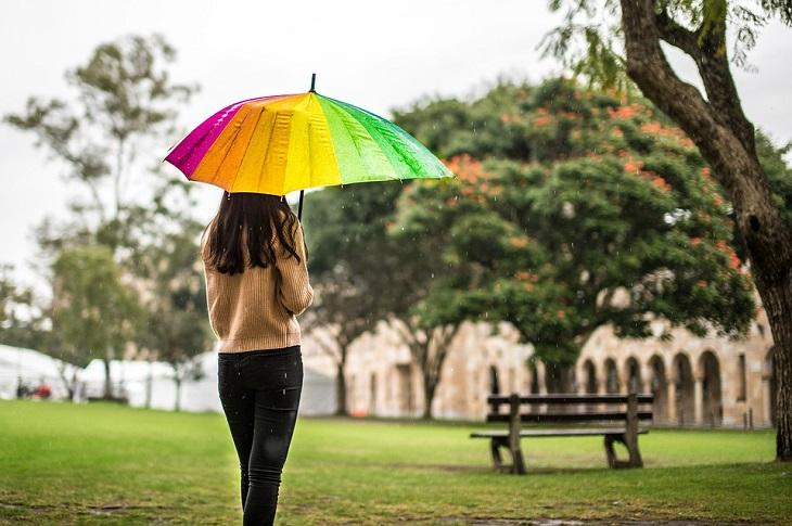 איך מזהים דיכאון בתפקוד גבוה: אישה מחזיקה מטרייה בפארק