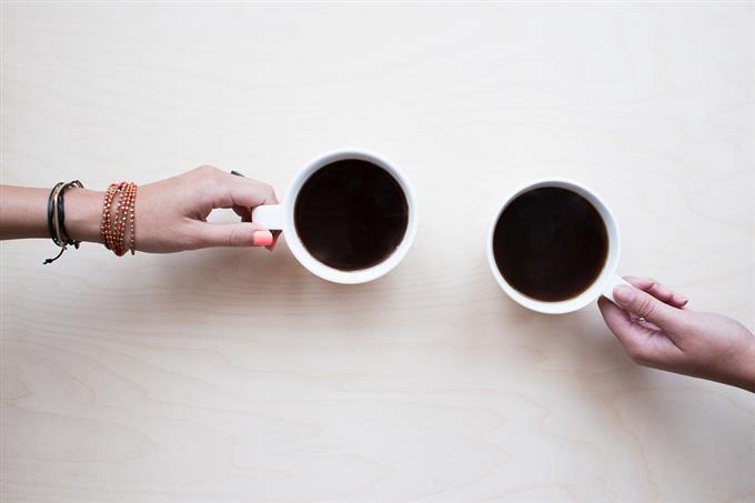 מבחן זוגיות: יד גברית ויד נשית מחזיקות כוסות קפה