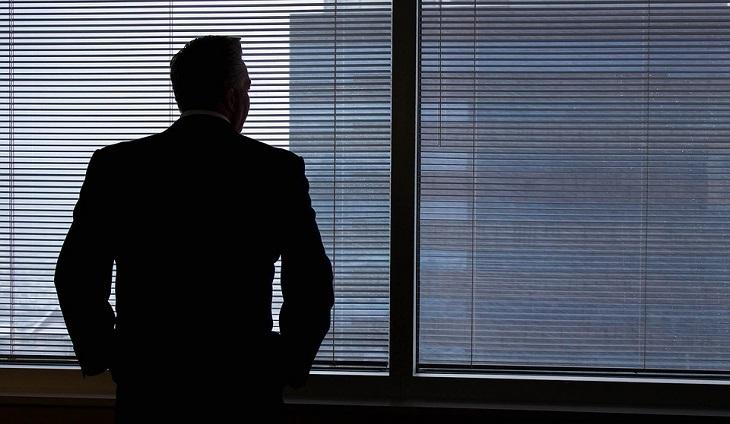 כלים לחיים מאושרים: גבר בלבוש עסקי מול חלון