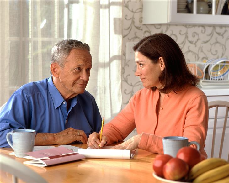 מצבים שצריכים להיות נחושים בשביל המשפחה: זוג מבוגר יושב ליד שולחן המטבח ומביט זה בזו