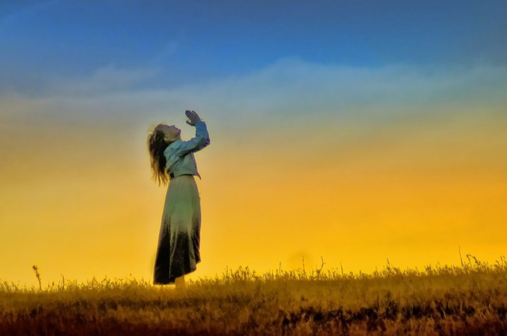 מהו מסע רוחני: ילדה מצמידה ידיים ומתפללת בשדה