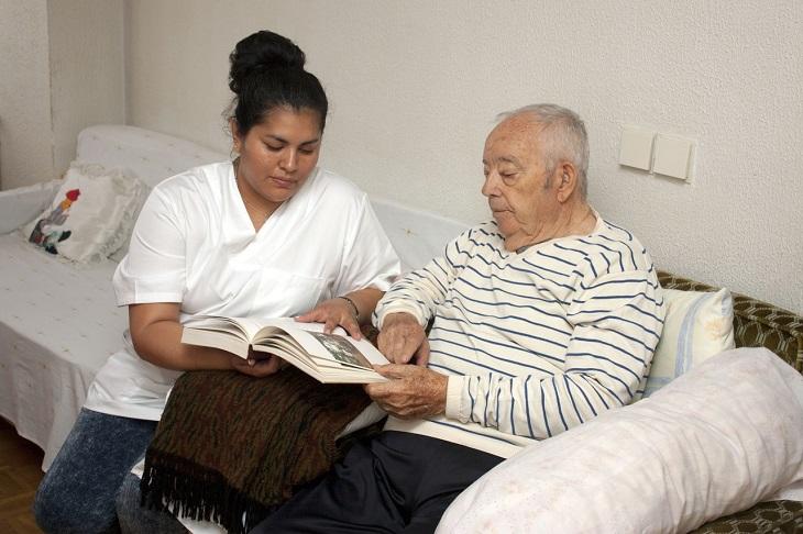 גמלת סיעוד של ביטוח לאומי: אישה עוזרת לאדם מבוגר לקרוא בספר