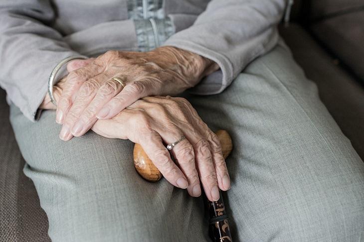 גמלת סיעוד של ביטוח לאומי: ידיים של אישה מבוגרת מונחות על מקל הליכה