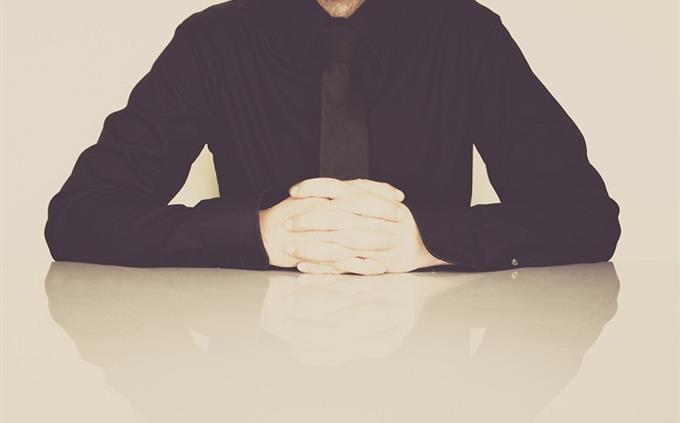 מבחן עברית: איש ישוב בחולצה מכופתרת ועניבה, כפות ידיו שלובות