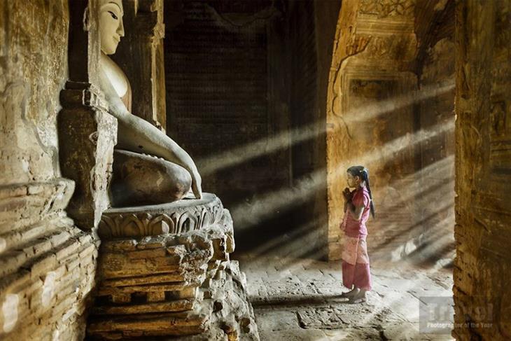 """תמונות מתחרות """"צלם הטיולים של השנה"""": ילדה עומדת ומתפללת לפסל בודהה במינאמאר"""