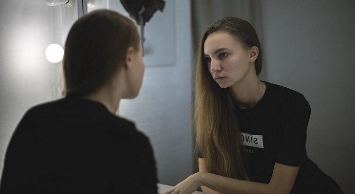 תכנים מומלצים 2018: אישה צעירה מתבוננת במראה