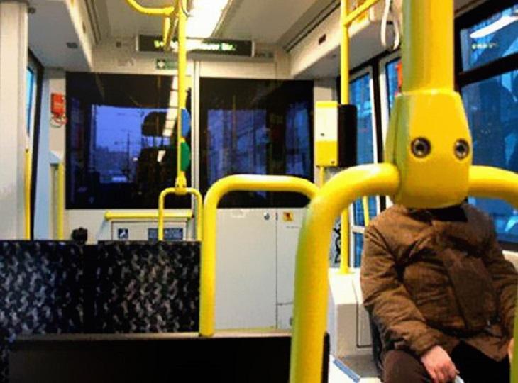 18 תמונות משעשעות: אדם יושב באוטובוס כאשר הצלם מצלם את התמונה כשהחיבור של העמוד הצהוב של האוטובוס מסתיר את פני הנוסע ונראים כמו פרצוף
