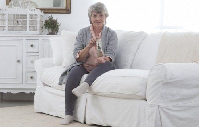 טיפול בכאבים: אישה מבוגרת מחזיקה מכשיר לייזר רך קטן ומתקדם
