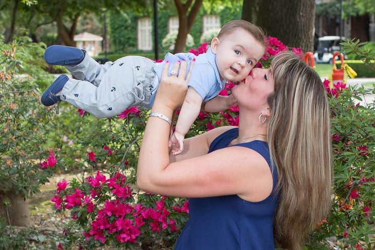 טיפים להורים: אמא מרימה את בנה לאוויר ומנשקת אותו