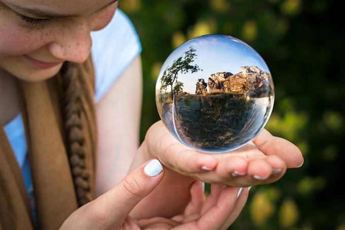 עד כמה החיים שלך זורמים: ילדה מסתכלת על נוף שמופיע בתוך כדור בדולח