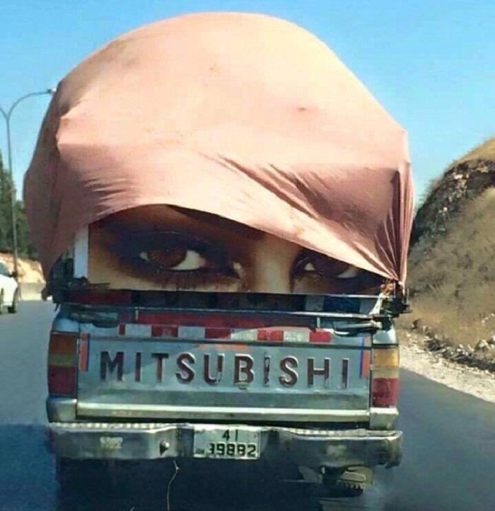 תמונות ברגע הנכון: טנדר עם שלטי פרסום של עיני אישה שמוסתרים על ידי כיסוי שעף עם הרוח