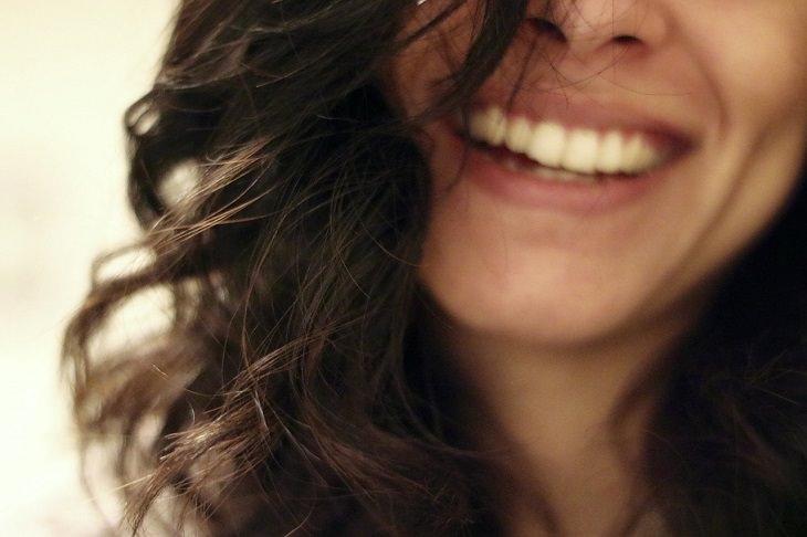 טריקים שעוזרים לקחת פיקוד במצבים בלתי נשלטים של הגוף: אישה צוחקת