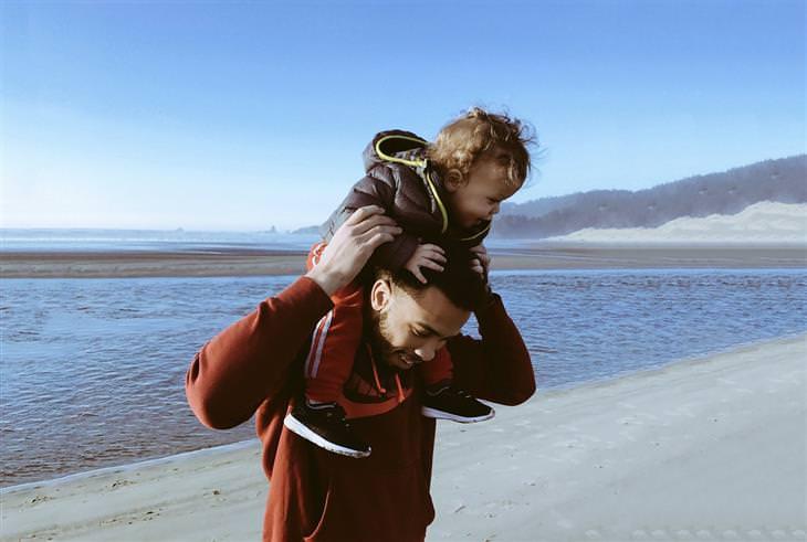 טיפים מרופאי ילדים להשגת שיתוף פעולה מהילדים: הורה מחזיק ילד על הכתפיים