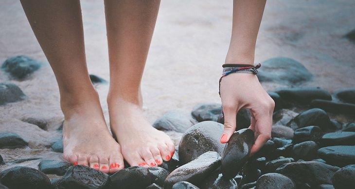 טיפול בפטרת ציפורניים: אישה יחפה הולכת על החוף