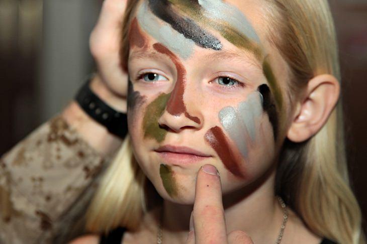 אירועי פורים 2018: ילדה צובעת את פניה בצבעי הסוואה