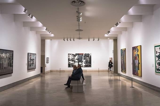 אנשים יושבים במוזיאון ומביטים בתמונות