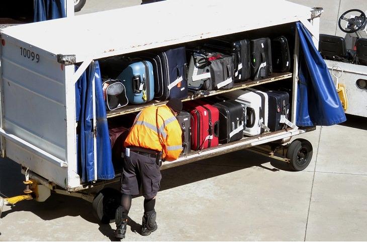 מדריך לטיסות לואו קוסט: סבל של נמל תעופה מעמיס מזוודות על עגלה במסלול נחיתה