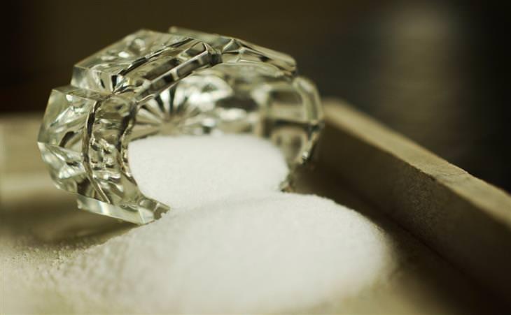 מידע ומחקרים על צריכת מלח: מלח נשפך מכלי זכוכית קטן על משטח