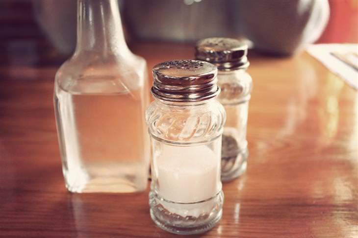 מידע ומחקרים על צריכת מלח: מלחייה ופלפליה ליד בקבוק מים, מונחים על שולחן