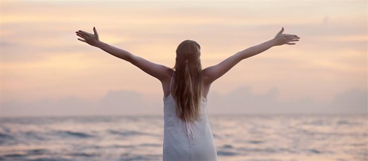 דברים שמונעים מכם אושר: אישה מרימה את ידיה לשמים מול הים