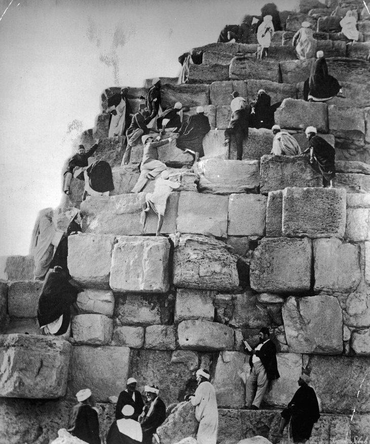תמונות היסטוריות: תיירים מטפסים בעזרת מדריכי הטיול שלהם, על הפירמידות של גיזה בשנת 1890 לערך