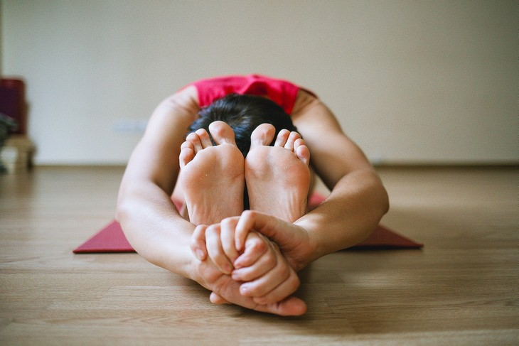 סימנים מוקדמים לדלקות מפרקים: גבר מתרגל תנוחת מתיחה על מזרן