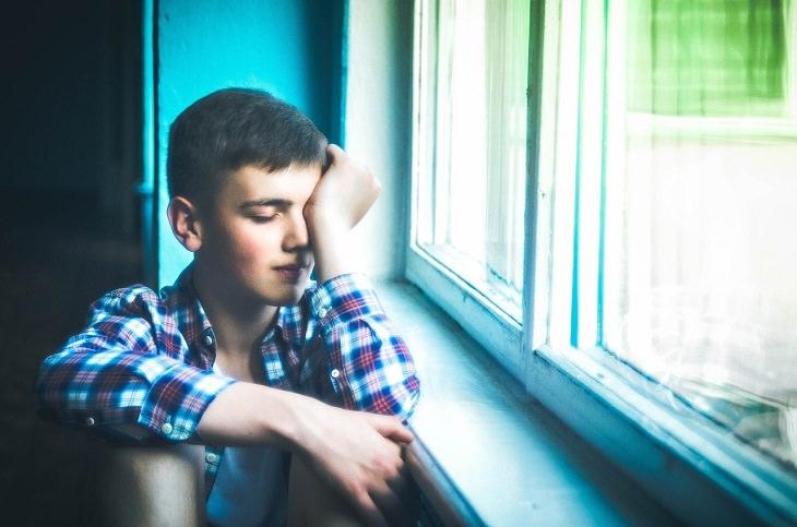 כך תזהו דכאון סמוי ותטפלו בו: צעיר יושב ליד החלון ומשפשף את עינו